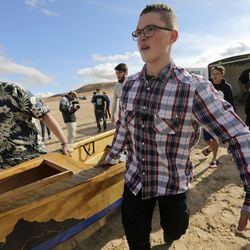 David Czeiszperger, a math teacher at Colorado's Platte Canyon High School, left, and Landon Pearce, a visually impaired 10th grader from the Utah Schools for the Deaf and the Blind, unload part of a boat from a trailer onto Lone Rock Beach at Lake Powell on Friday, March 26, 2021. The piece they are unloading was originally built by the Platte Canyon High School Yacht Club and donated to the Utah Schools for the Deaf and the Blind Yacht Club, so the Utah students could model their own boat off of Platte Canyon's model.