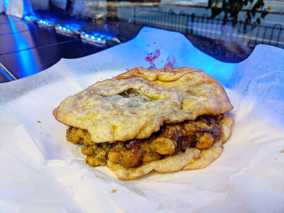 A serving of doubles —spicy and sweet chickpeas sandwiched between two pieces of fried dough —sits on white paper on a counter, illuminated by a glowing blue light