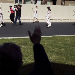 Neighbors wave as Ann and Enoch Bell walk the neighborhood after their ceremony in Kaysville on Friday, April 24, 2020.