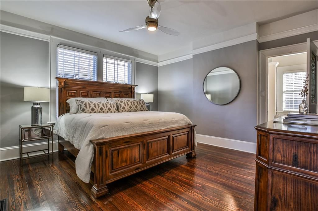 A large gray bedroom with a ceiling fan and wooden bed.