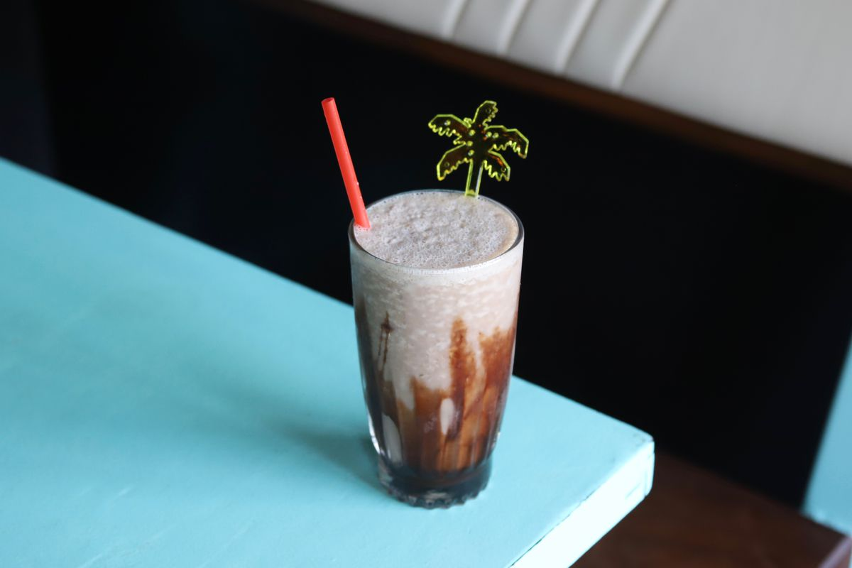 A frozen mudslide cocktail sits on a turquoise table. It's garnished with a small plastic palm tree.