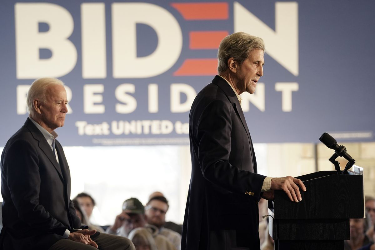 Kerry speaks at a podium, with Biden looking on.