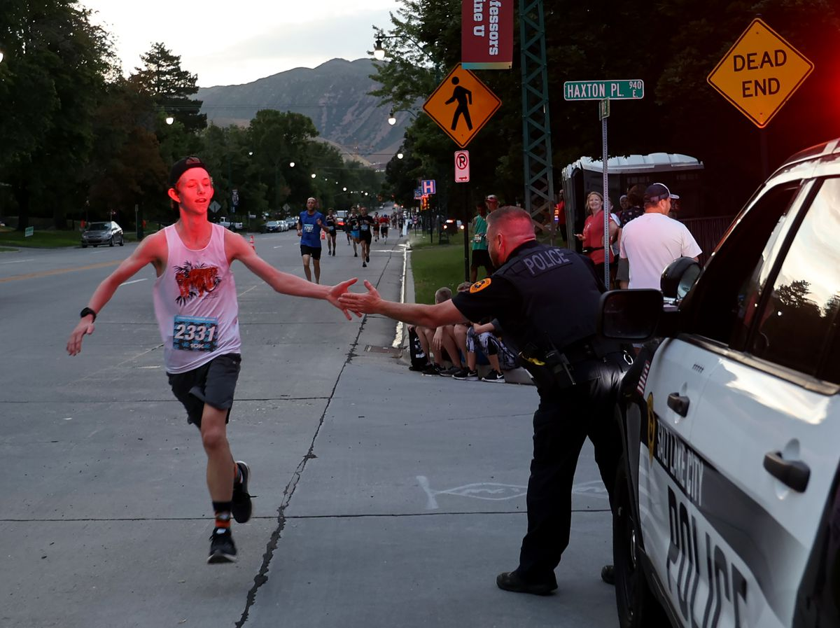 Thomas Stark gives a Salt Lake City Police officer a side-five as he runs in the Desert News 10K in Salt Lake City on Friday, July 23, 2021.