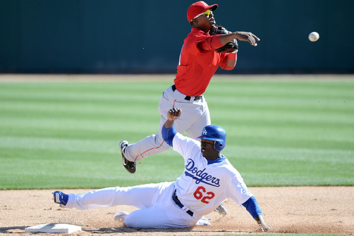 Jean Segura of the Los Angeles Angels turns a double play in front of a sliding Trayvon Robinson of the Los Angeles Dodgers during spring training at Camelback Ranch on February 27, 2011 in Phoenix, Arizona.  (Photo by Harry How/Getty Images)