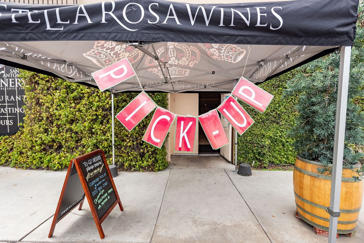 """A view from the sidewalk into the winery, which is covered in ivy, with a big sign reading """"PICK-UP"""" and a chalkboard sign and a potted plant in the foreground."""