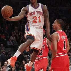 New York Knicks' Imam Shumpert goes up to the net past Chicago Bulls' Derrick Rose, right, during the first half of an NBA basketball game, Sunday, April 8, 2012, at Madison Square Garden in New York.