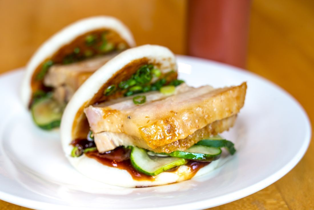 Slices of pork belly sit in a white bun with greens and hoisin sauce.