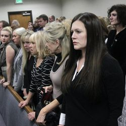 Alexis Somers, right, her sister Rachel MacNeill, upper right, and family members rise for the jury to take their place for closing arguments in the murder trial of former Pleasant Grove physician Martin MacNeill in Provo's 4th District Court on Friday, Nov. 8, 2013. MacNeill is charged with murder in the 2007 death of his wife, Michele MacNeill.