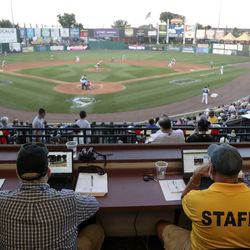 Ron Besaw, right, operates a laptop computer as home plate umpire Brian deBrauwere, gets signals from radar with the ball and strikes calls during the fourth inning of the Atlantic League All-Star minor league baseball game.