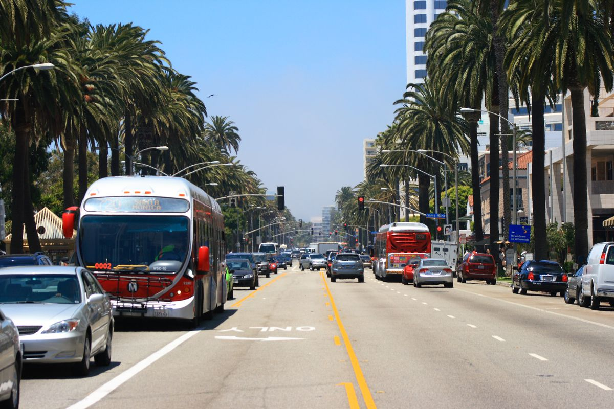 Red buses and sedans on a palm-tree-lined street in Santa Monica.