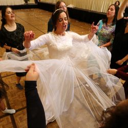 Chaya Zippel dances with female guests after marrying Rabbi Mendy Cohen in a traditional Chabad Lubavitch Jewish wedding at the Grand America Hotel in Salt Lake City on Monday, Sept. 12, 2016. The men and women celebrate in different areas.