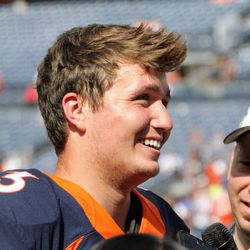 Drew Lock, the Broncos rookie QB, smiles while speaking with media after practice.