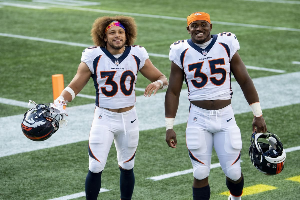 Phillip Lindsay #30 and Jeremy Cox #35 of the Denver Broncos celebrate a victory against the New England Patriots at Gillette Stadium on October 18, 2020 in Foxborough, Massachusetts.