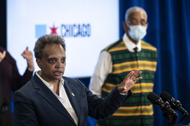 Mayor Lori Lightfoot at a Thursday press conference, vowing to discipline a group of Chicago police officers seen on video lounging in the burglarized campaign office of U.S. Rep. Bobby Rush (right).