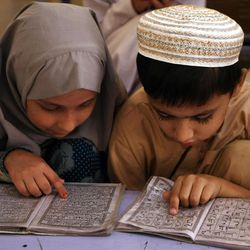 Pakistani children read together from Muslim's holy Quran, during their lessons at a local madarassa, or religious school,  in Karachi, Pakistan on Saturday, March 6, 2010. (AP Photo/Fareed Khan)