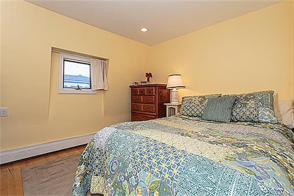 A bedroom with a bed next to a nightstand next to a dresser.