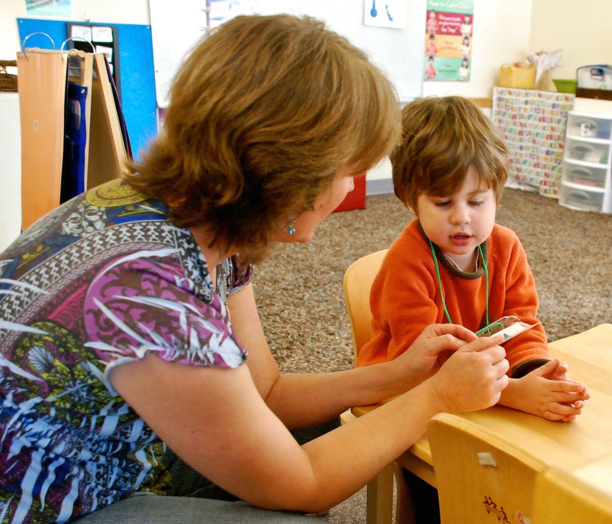 Speech therapist Melissa Cain talks to a preschooler at the Bal Swan Children's Center.