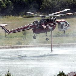 A helicopter dips to fill with water to fight the fire in New Harmony on Sunday. Eleven structures burned over the weekend, but no injuries have been reported.