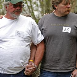 Tuck Nipko, left, and his cousin Ed Goble, both cancer patients, hold hands during the closing ceremony of the Reel Recovery fly-fishing retreat at Falcon's Ledge lodge.