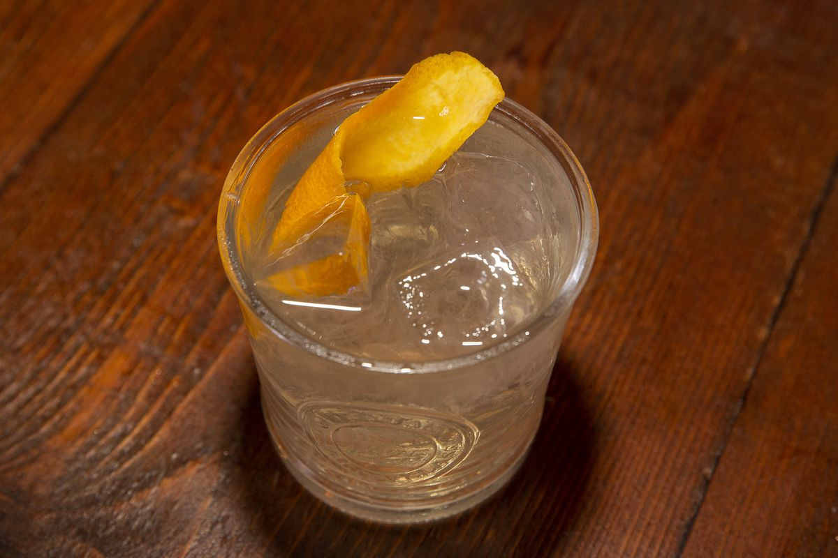 A short, clear glass holding a clear cocktail with an orange twist