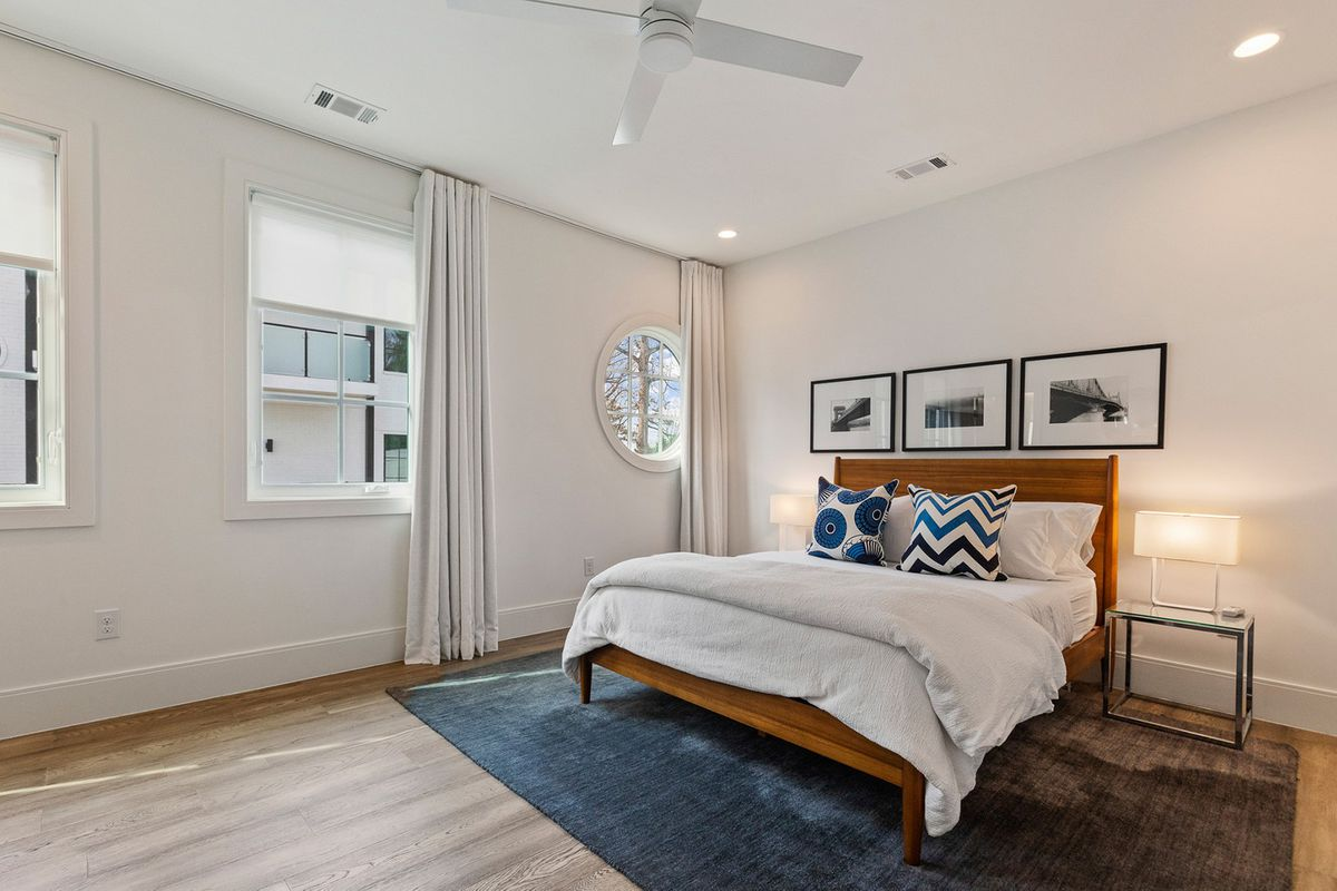 A large white bedroom with a white ceiling fan.