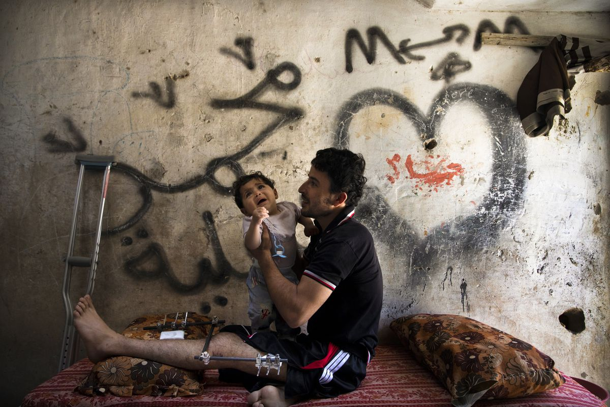 May 24: Samir Suliman Asaliah 29, plays with his baby son, Nasir on in Gaza city, Gaza strip. He was shot in his knee with an exploding bullet on April 6, 2018. Read More. (Paula Bronstein/Getty Images)