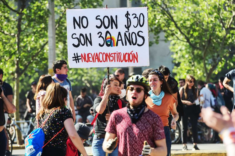 """A protester in Chile holds a sign reading, """"No son $30, son 30 anos #nuevaconstitucion."""""""