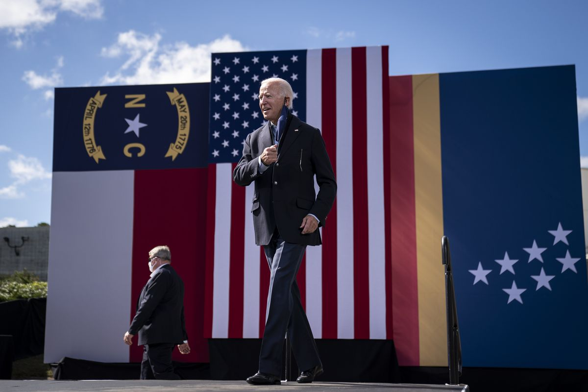 Biden pulls off a navy face mask as he mounts an outdoor podium, giant North Carolina, USA, and Durham flags behind him. The NC flag features red and white horizontal stripes, and the Durham flag a blue field with narrow red and yellow stripes at the bottom; 7 white stars are scattered across the blue field.