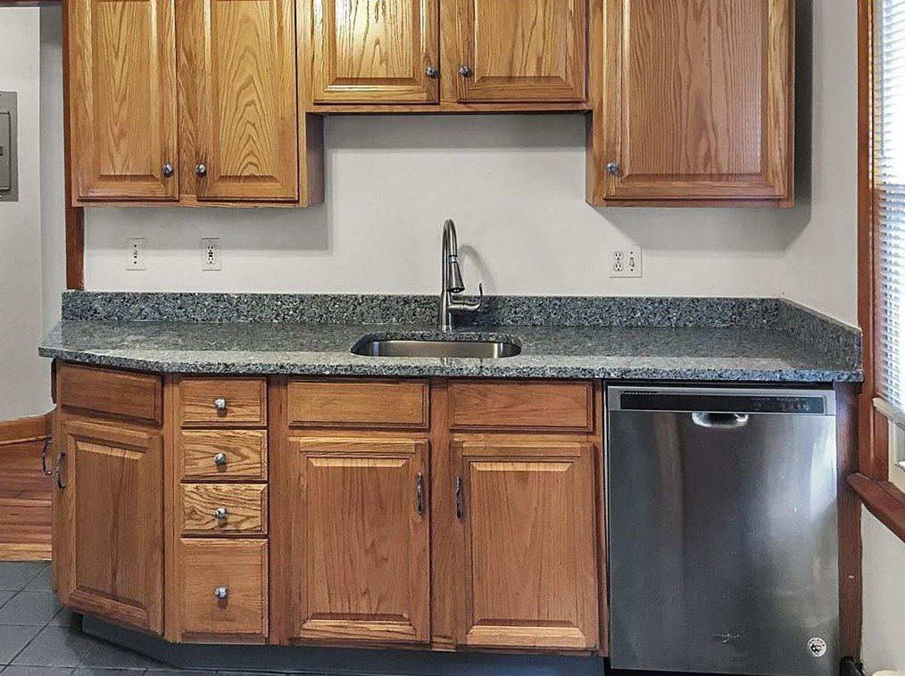 A closeup of a kitchen counter with a sink and there's cabinets above it.