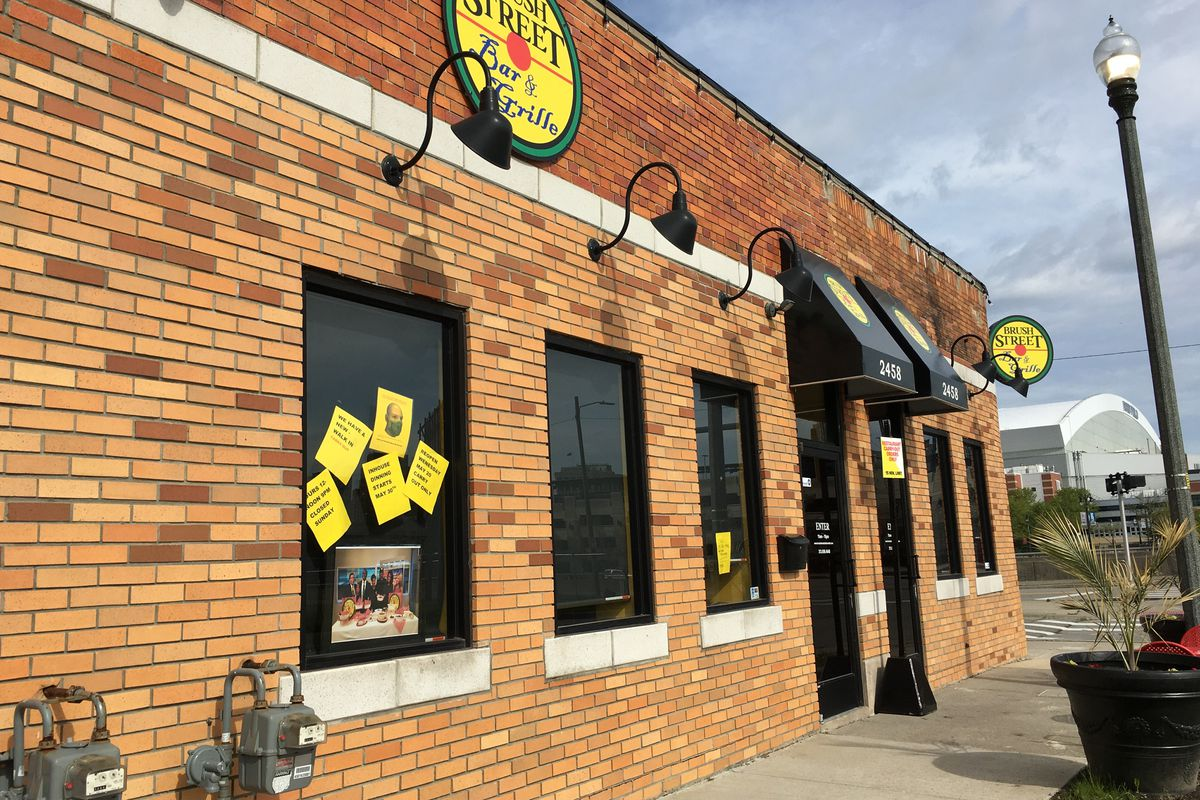 Brush Street Bar & Grille is located in a brick building with a curved corner storefront. The restaurant is shown on a sunny day with yellow paper signs plastered in the windows related to coronavirus operations.