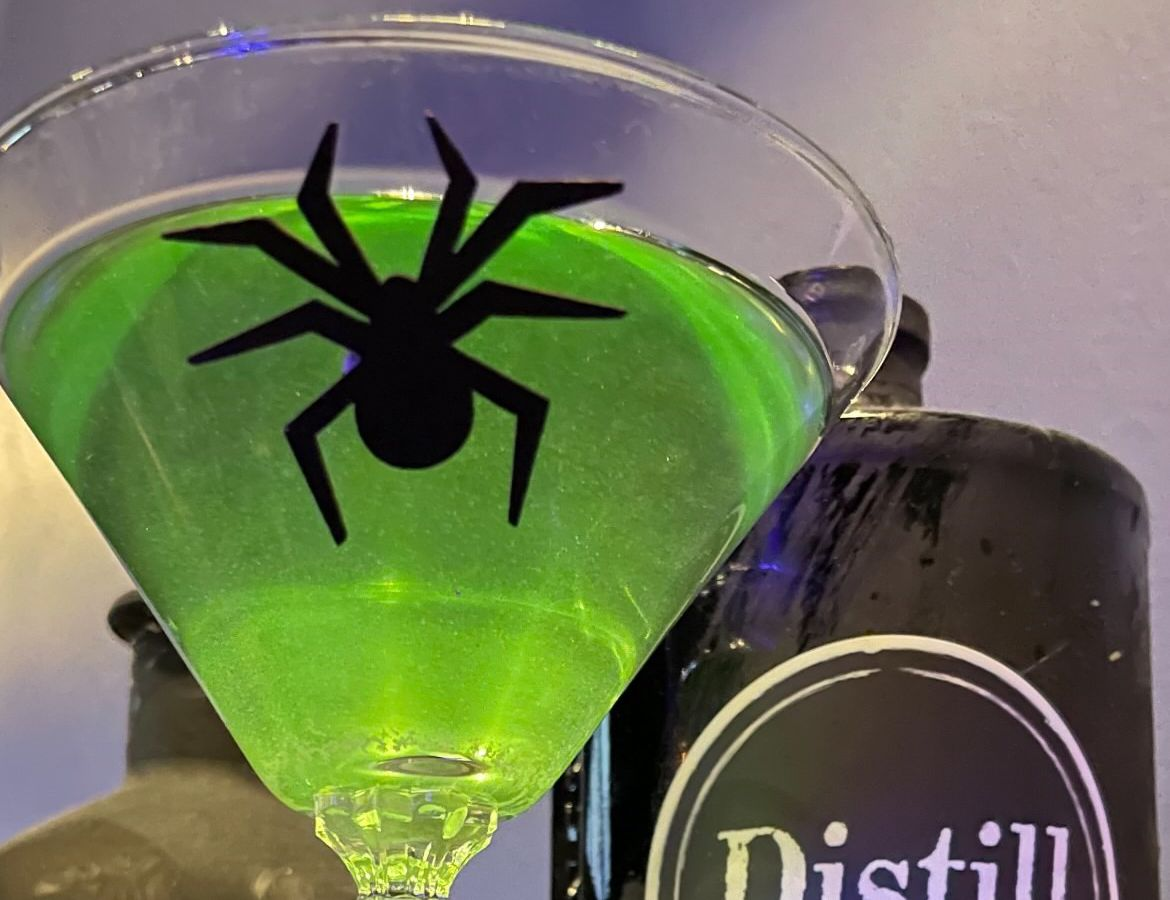 A green martini with a spider on it.