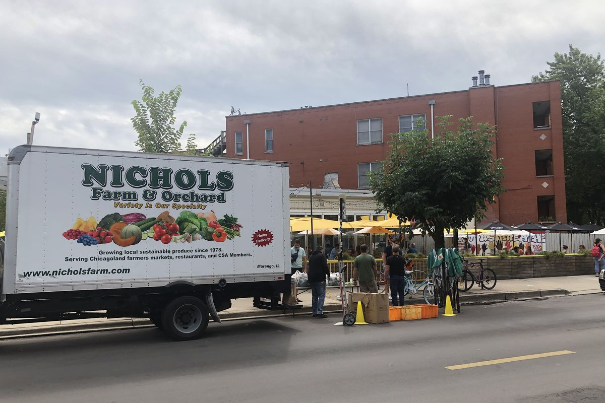 A truck in front of a storefront.