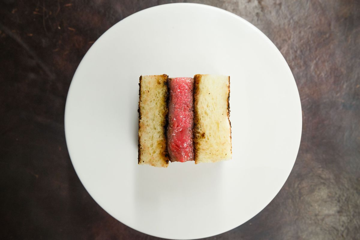 a wagyu sandwich — pink meat between crustless slices of white bread — sits on a white plate.
