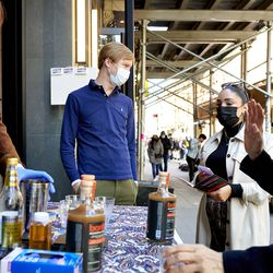 Douglas Watters speaks with customers at a sidewalk tasting at Spirited Away, Watters' alcohol-free bottle shop, in the Lower East Side of Manhattan in New York on Saturday, March 13, 2021. The shop is devoted to everything needed to make alcohol-free cocktails.