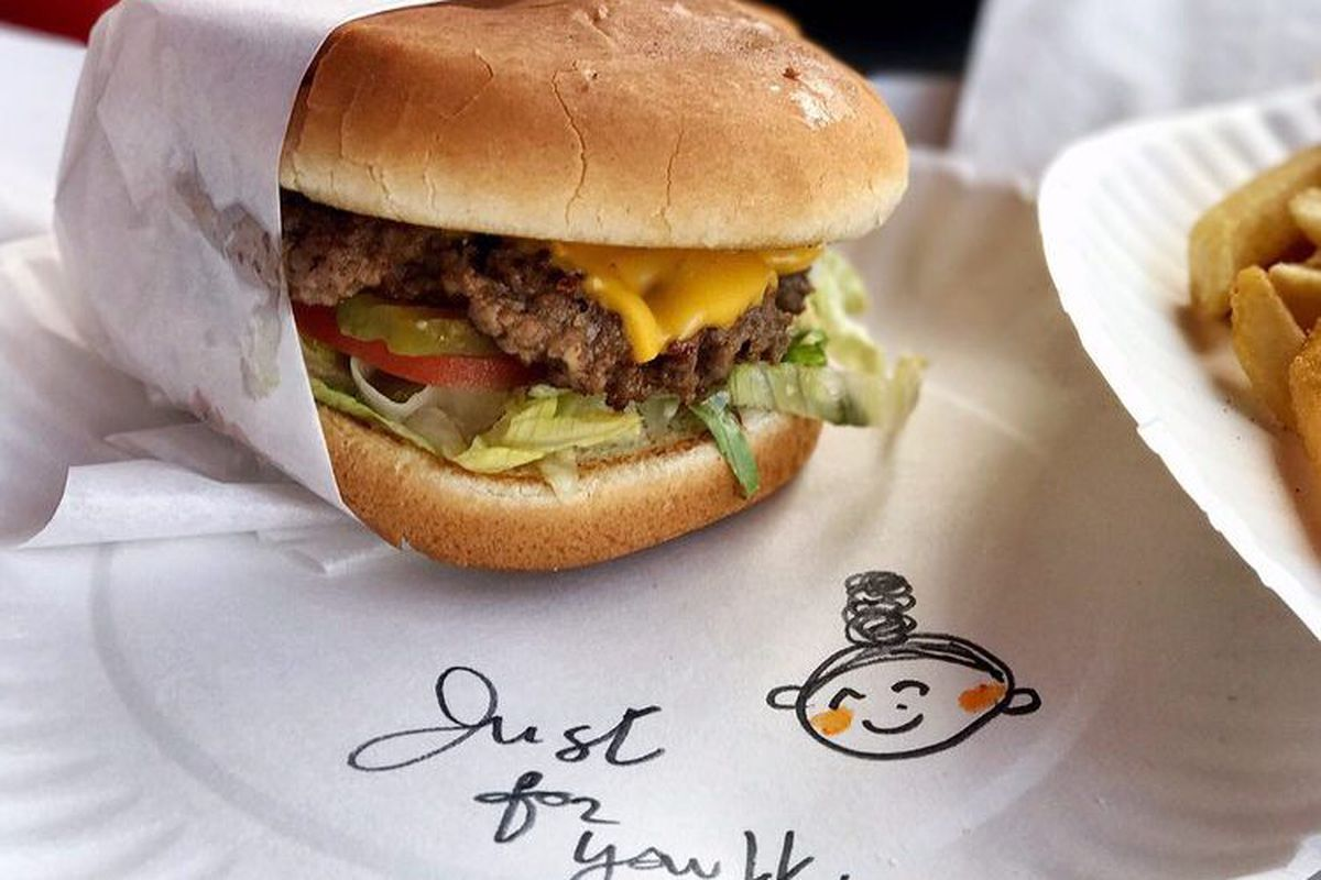 A burger on a plate with a hand-drawn note of thanks.