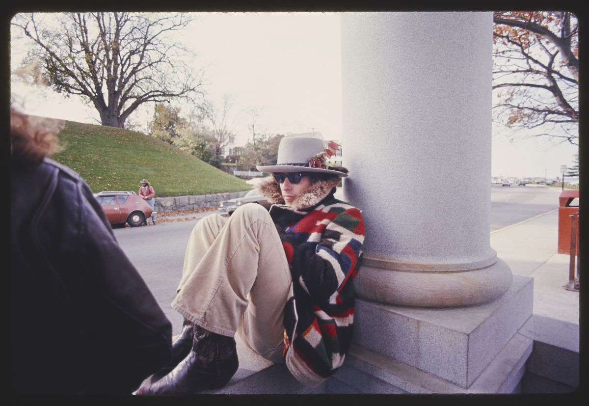 Bob Dylan in a colorful jacket sitting by a building column in Rolling Thunder Revue