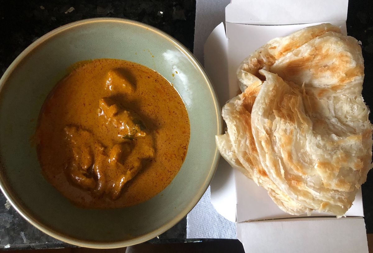 A green bowl filled with orange curry with folded roti on a white cardboard box to the side of the bowl