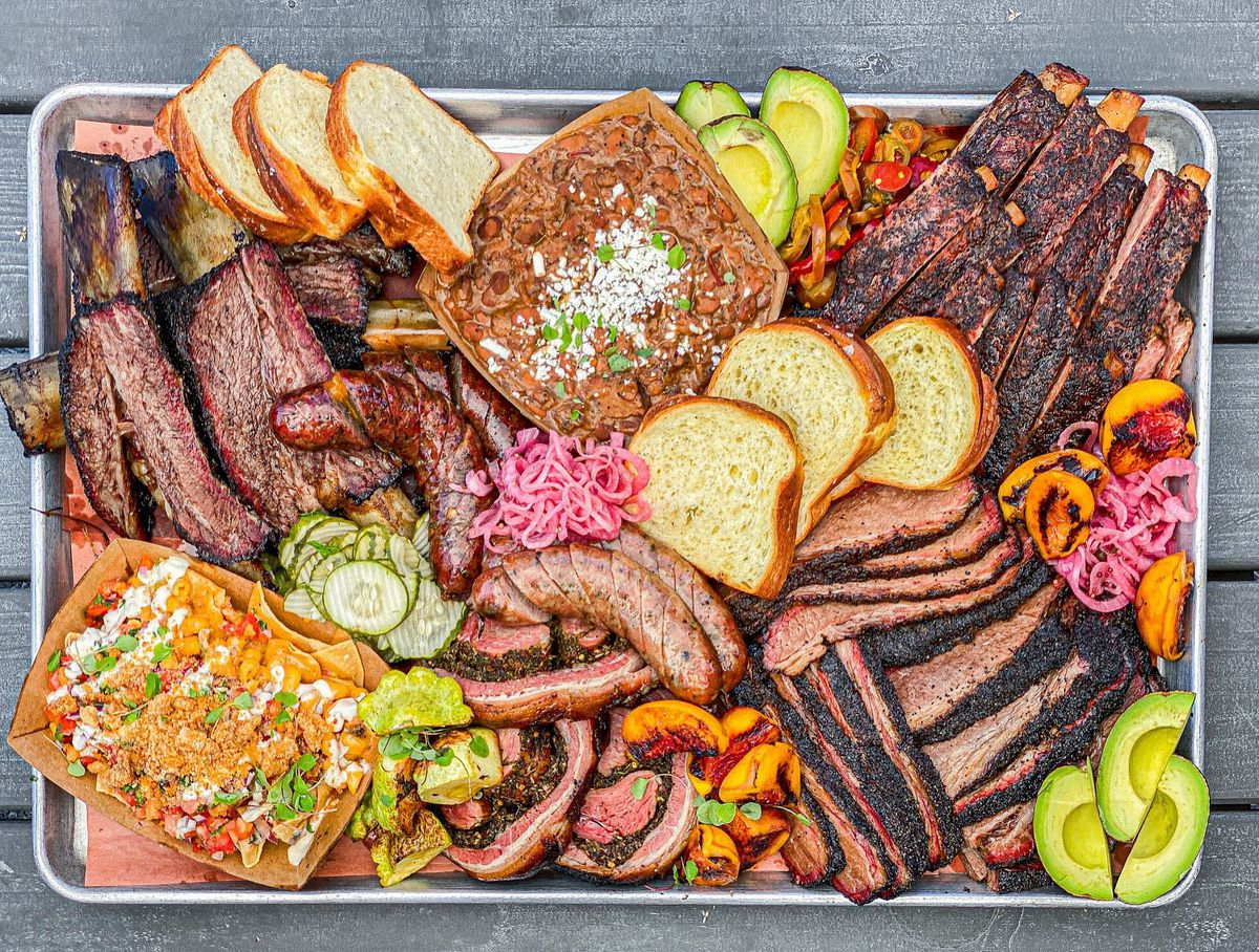 A tray full of barbecued meats like brisket and ribs.