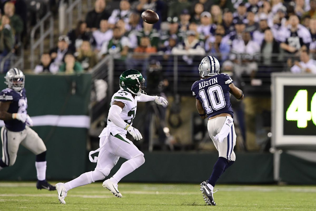 Tavon Austin of the Dallas Cowboys catches a pass under pressure from Brian Poole of the New York Jets at MetLife Stadium on October 13, 2019 in East Rutherford, New Jersey.