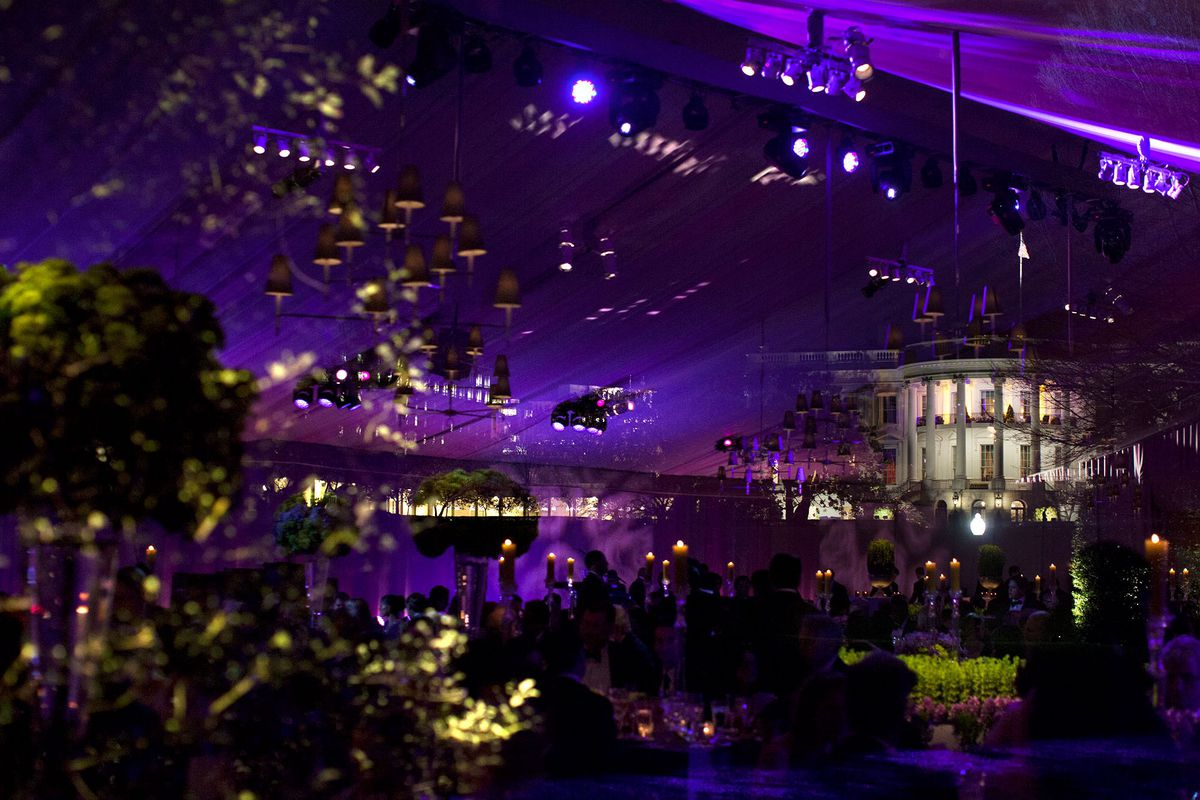 The White House is reflected in the window of a large tent lit with purple lights
