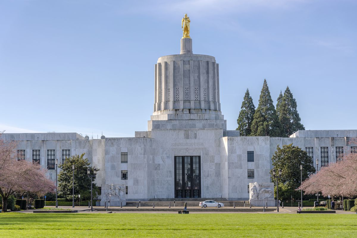 The exterior of the Oregon State Capitol. The facade is white and grey. There is a domed tower with a gold statue on top. There is a lawn in the foreground.