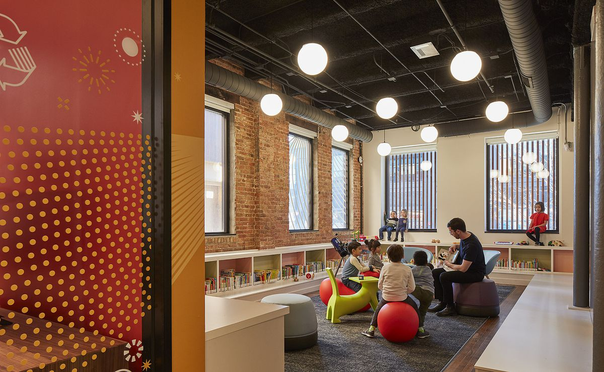 A group of children sit around an adult reading a story in a corner room with globe lights, five windows, and low shelves lined with books.