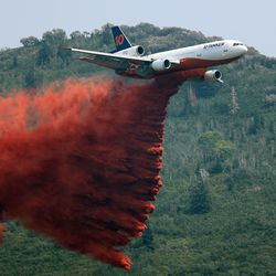 A large tanker drops retardant as crews continue fighting the Parleys Canyon Fire near Park City on Sunday, Aug. 15, 2021.