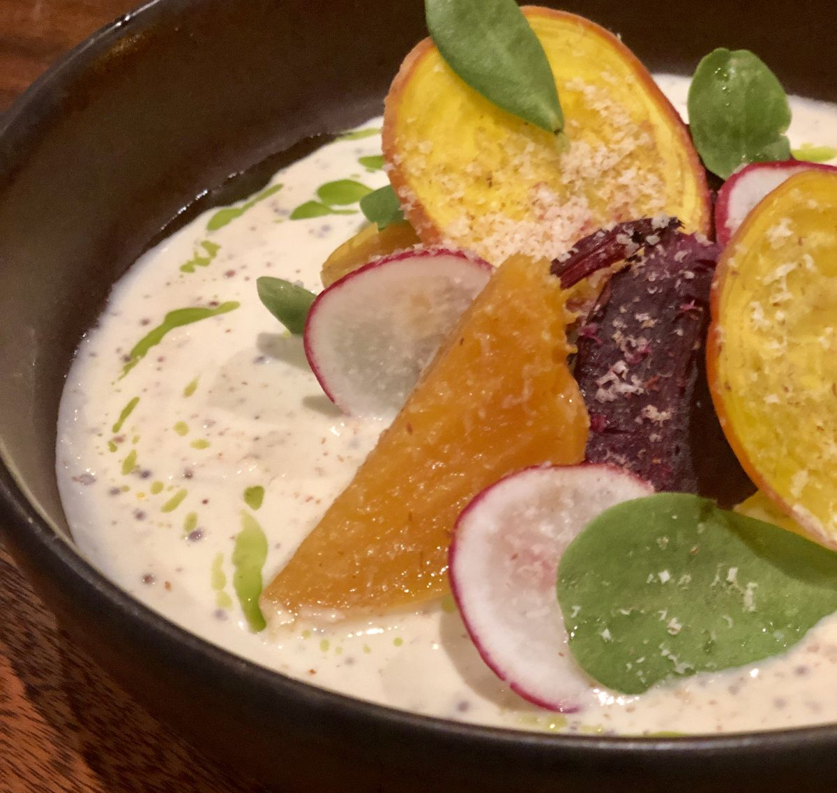 A beets salad in a circular bowl sitting in cheese fondue.