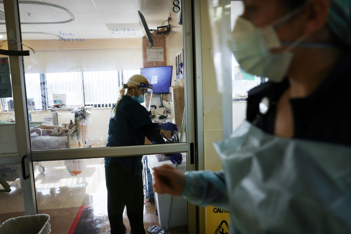 an environmental services provider cleans the room of an ICU Covid-19 patient