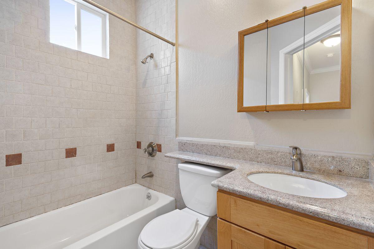 A bathroom with bath tub, toilet, sink, and window.