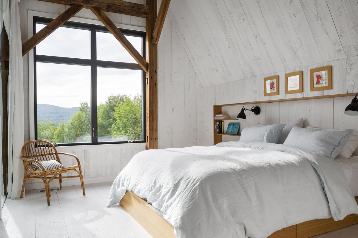 A white walled bedroom with view of rolling landscape outside. The bed is white and sits on a wooden platform.
