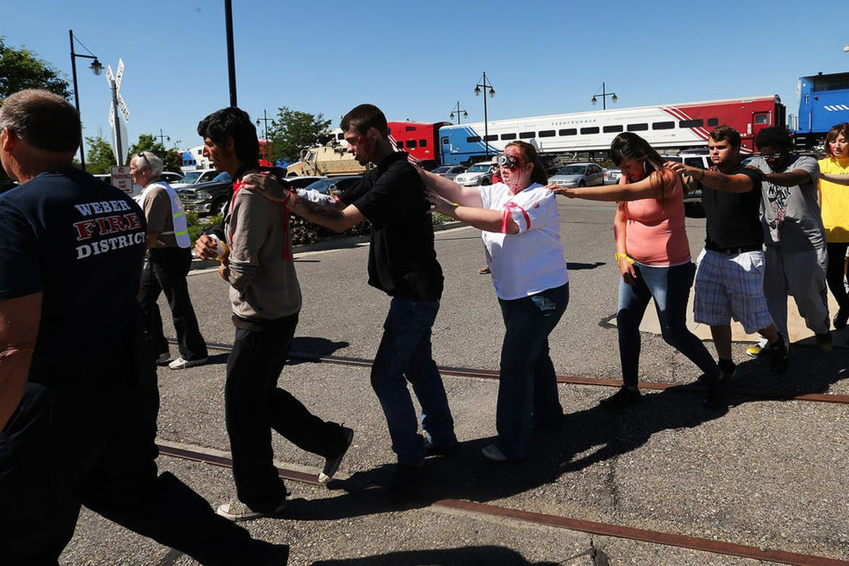 """Injured """"victims"""" are led from a train during a full-scale emergency response drill simulating a terrorist suicide bombing on FrontRunner in Ogden on Wednesday, June 28, 2017. Emergency personnel from a wide variety of agencies — including the Utah Transi"""