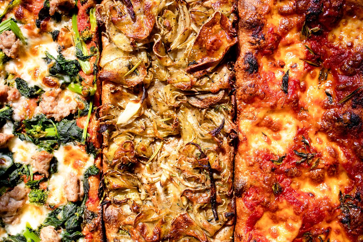 three rectangular pizzas up-close, one with broccoli rabe and pork, the middle with mushrooms and cheese, the third plain with tomato sauce