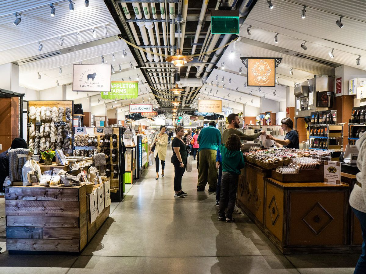 An interior shot of Boston Public Market shows customers shopping at several different vendors' stands